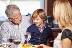Family with smiling grandfather and his grandchild eating out in